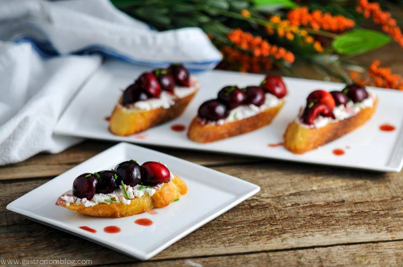 Cherry Crostini with goat cheese on a white plate, white napkin and flowers in background