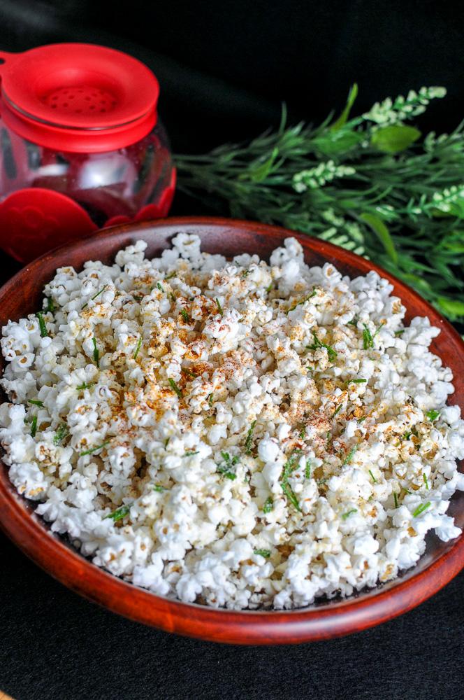 Popcorn in wooden bowl. flowers behind