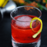 Red cocktail in rocks glass, lemon peel