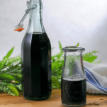 Dark syrup in 2 bottles, greenery behind