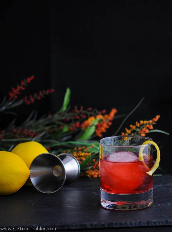The Boulivardier cocktail in rocks glass with jigger, flowers and lemons in background