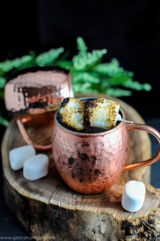 The Campfire Mule cocktail in copper mugs with toasted marshmallows and flowers in background