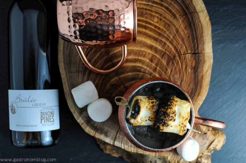 The Campfire Mule cocktail in copper mugs with Brulee Liqueur bottle and wooden plate