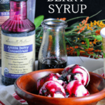 Purple syrup on top of ice cream in wooden bowl, aronia bery bottle, glass jar and flowers in background