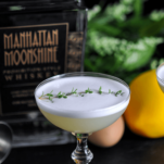 White foam topped cocktail in coupe, thyme on top, whiskey bottle, lemon and greenery in background