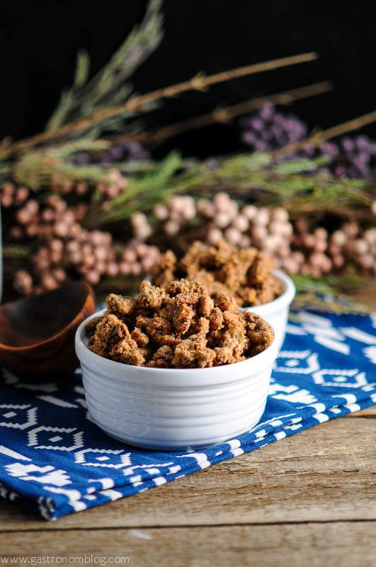 Bourbon Candied Pecans, these roasted nuts in white ceramic bowl on blue and white napkin, wood spoon and flowers in background