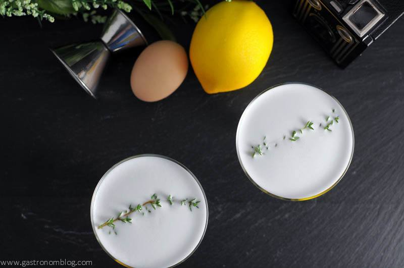 Thyme to Shine Cocktail in coupes, overhead shot with lemons, egg and jigger