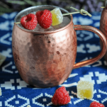 Cocktail in copper mug, raspberries and candied ginger around, blue and white napkin