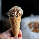 tan ice cream in a cone, hand holding
