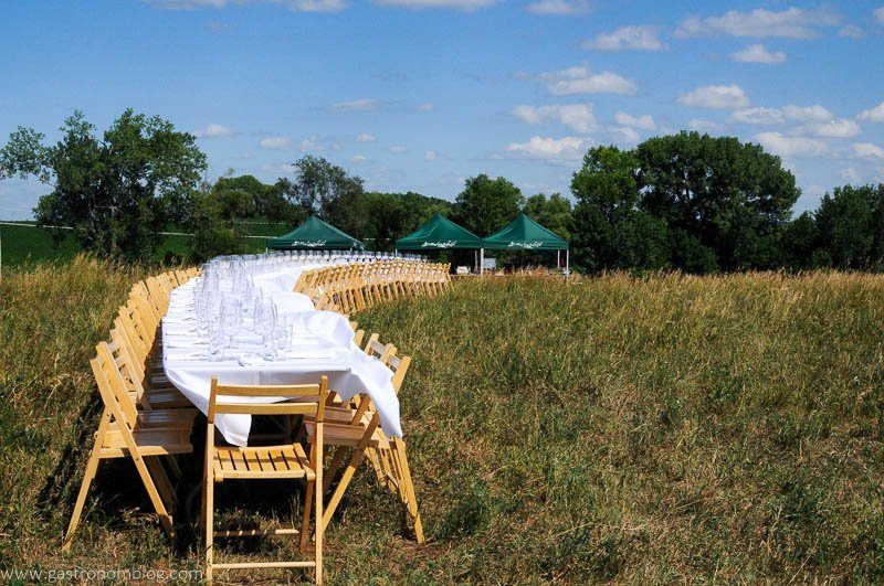 Long table with wooden chairs in a field with a white cloth