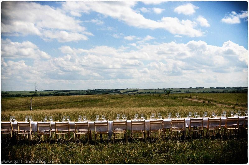 Field with wooden chairs in a field. Covered with a white tablecloth