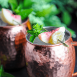 Peach cocktail in copper mug with basil