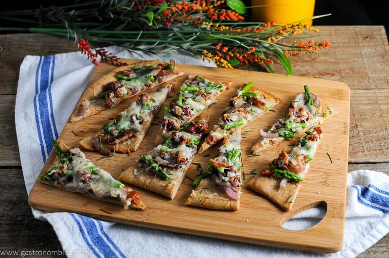 Bacon and Blue Cheese Flat Breads on wood cutting board. White napkin and flowers in background