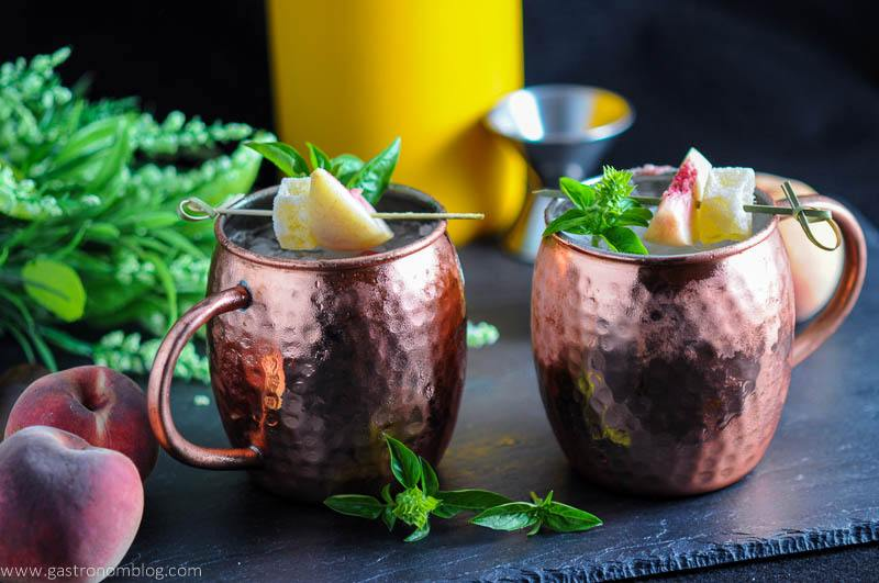 Peach and Basil Moscow Mule in copper mugs. Peaches, flowers, yellow container and jigger in background