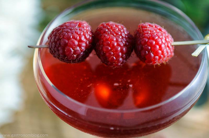Raspberry Manhattan Cocktail in coupe glass with raspberries on cocktail pick