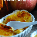 Creme Brulee in white ramekins, apples and leaves behind