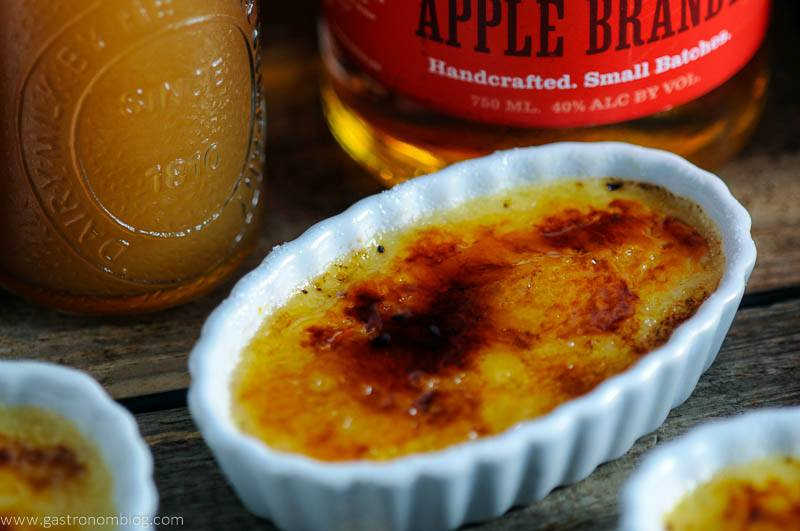 Apple Cider Brandy Creme Brulee in ceramic baking dishes. Jar of cider and Apple brandy bottle in background