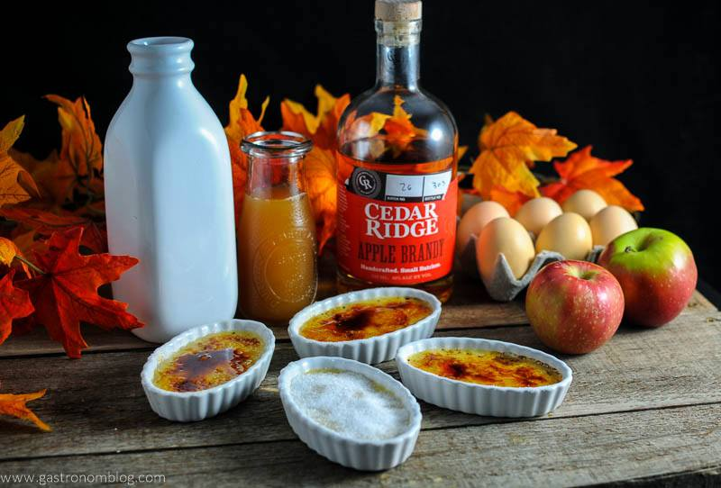 Apple Cider Brandy Creme Brulee in white ramekins, white bottle, jar of apple cider and apple brandy bottle, apples and eggs in background. Fall leaves