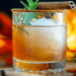 Cocktail in a rocks glass with cinnamon and rosemary garnish