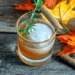 Cocktail in a rocks glass with cinnamon and rosemary trim, fall leaves in background