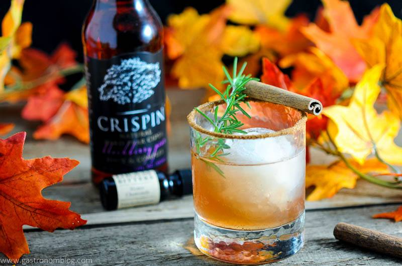 The Autumn Pea Cocktail in rocks glass with rosemary and cinnamon stick. Bottle of bitters and pear cider in back with fall leaves