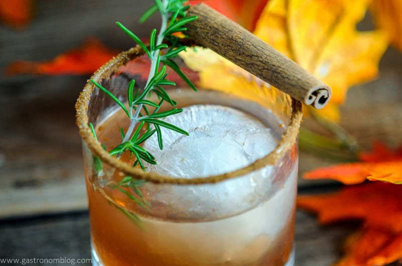 The Autumn Pear cocktail in rocks glass with cinnamon stick and rosemary. Fall leaves