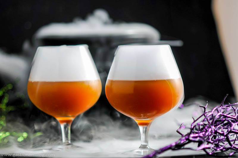 Bourbon Butterbeer Cocktails in brandy snifters. Dry ice in cauldron behind