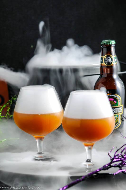 Bourbon Butterbeer Cocktails in brandy snifters. Ginger beer bottle and dry ice in cauldron behind