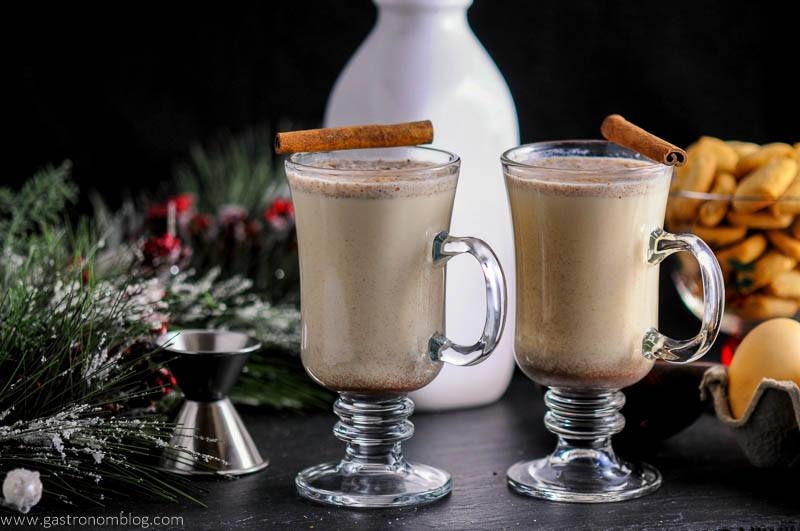 Salted Butterscotch Bourbon Eggnog in glass mugs with cinnamon sticks. Jigger, fir branch, milk bottle and cookies in background
