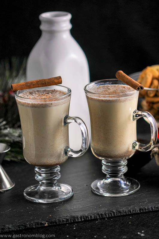 Salted Butterscotch Bourbon Eggnog in glass mugs, cinnamon sticks, milk bottle with cookies in the background