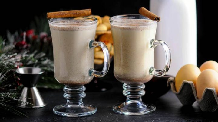 Salted Butterscotch Bourbon Eggnog in glass mugs with cinnamo sticks. Eggs, jigger, white jug in background
