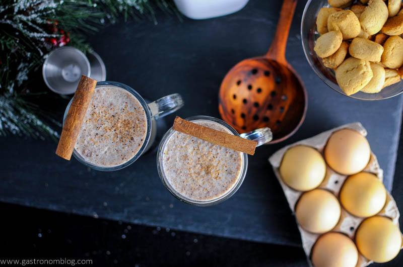 Salted Butterscotch Bourbon Eggnog top shot with cinnamons ticks, wooden spoon, jigger, cookies and eggs