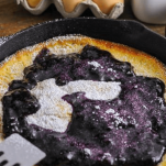 Pancake in cast iron skillet, blackberry sauce and powdered sugar