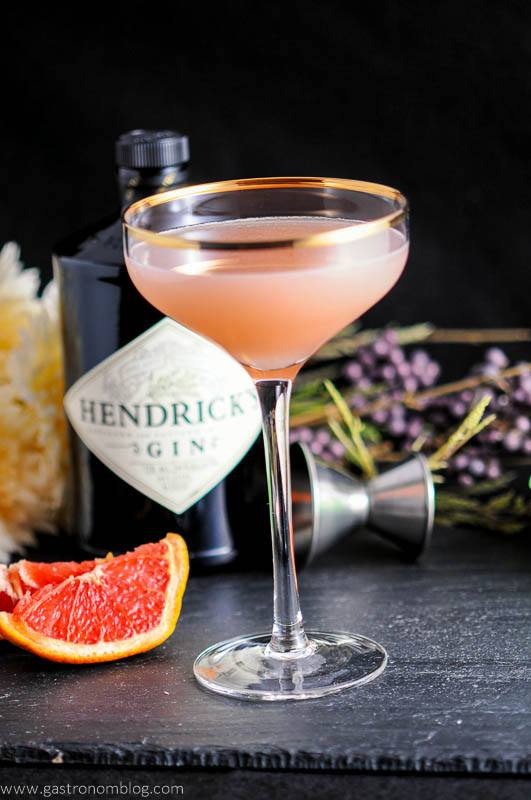 The Pink Pear cocktail, gold rimmed coupe, grapefruit wedges, jigger, gin bottle and flowers in backgrond