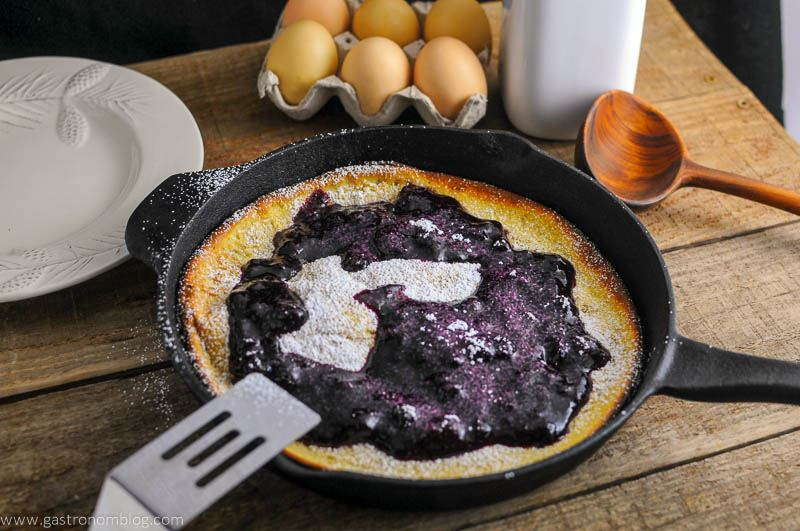 Dutch Baby Pancake with Blueberry Whiskey Sauce in skillet with spatula, wooden spoon, white plate, eggs and milk bottle in background