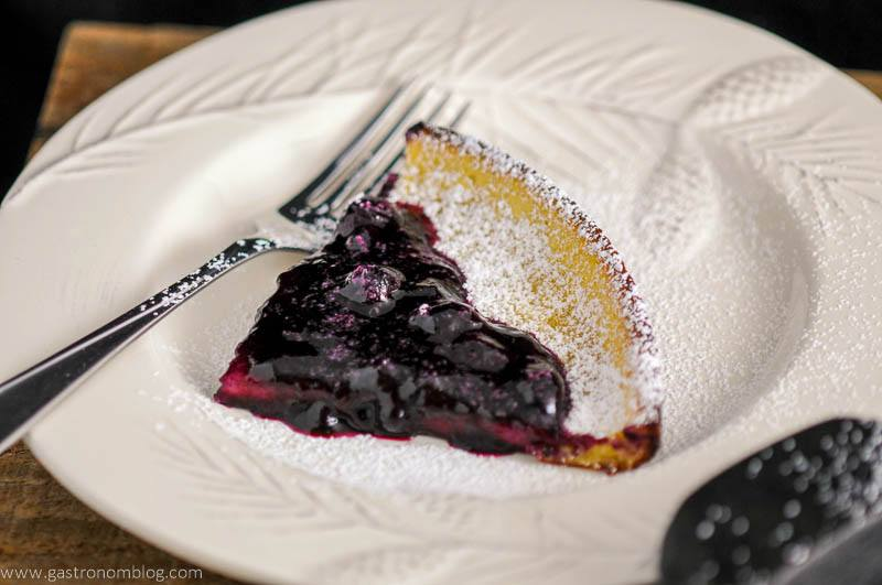 Dutch Baby Pancake with Blueberry Whiskey Sauce on white plate with fork