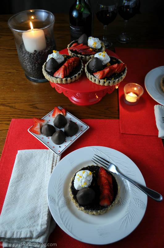 Chocolate Bourbon Tart with Strawberries, place settings on red placemats with candles