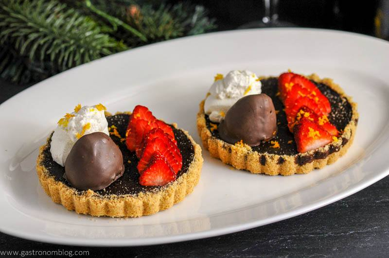 Chocolate Bourbon Tart with Strawberries on white platter
