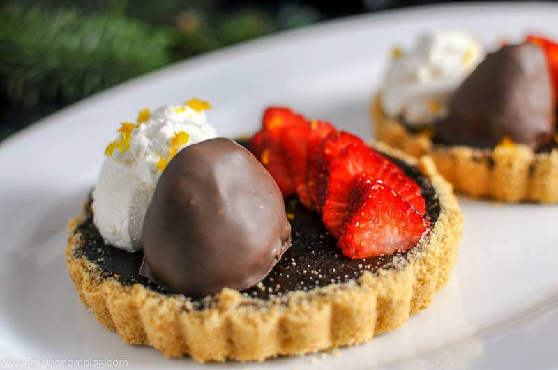 Chocolate Bourbon Tart with Strawberries on a white plate