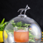 Pink cocktail in rocks glass with glass domb over the top