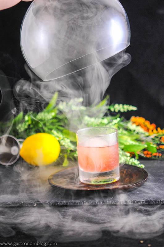 The Smoked Cherry cocktail in rocks glass, cloche over the top with smoke coming out. Lemon and flowers in background