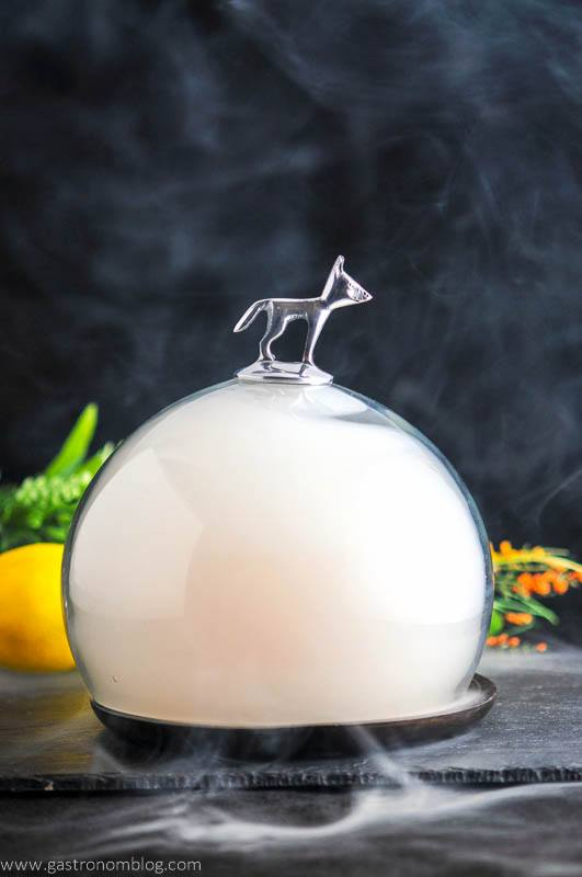The Smoked Cherry cocktail under smoke filled cloche with silver fox on top.