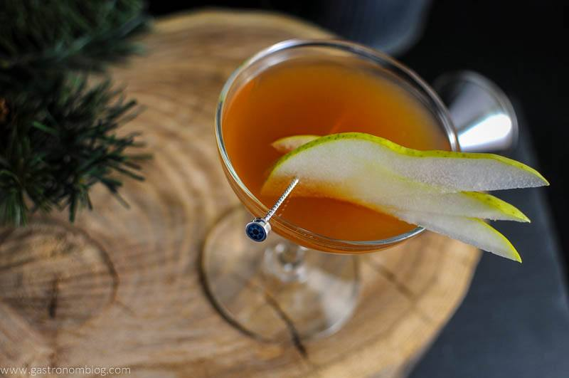 The Peaty Pera cocktail with pear slices on a cocktail pick on a wood plate