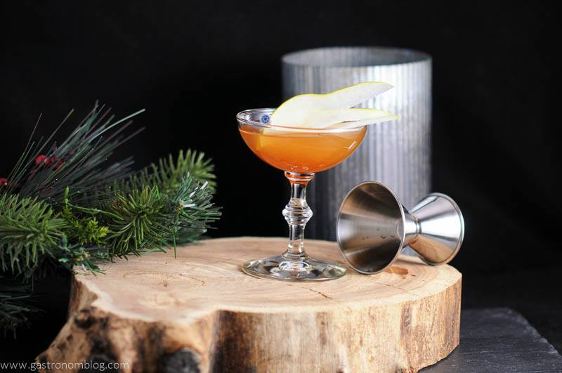 The Peaty Pera cocktail in coupe on wood plate. Jigger, metal canister, fir branch in backgrund