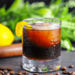 Brown cocktail in rocks glass, lemon peel