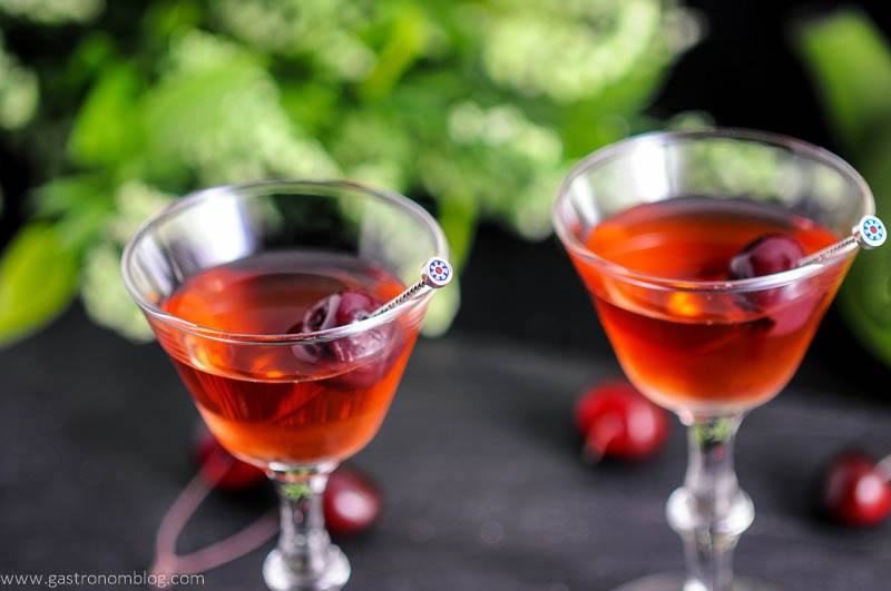 The Cherry Blossom Cocktail in two cocktail coupes with cherries on cocktail picks