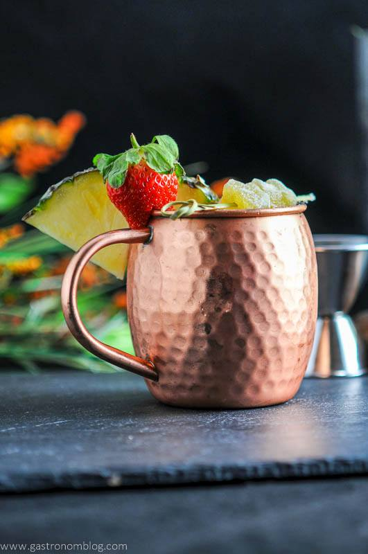 Spicy Pineapple Strawberry Moscow Mule in copper mug with ginger, strawberries and pineapple wedge. Jigger in background