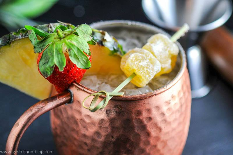 Spicy Pineapple Strawberry Moscow Mule in copper mug with strawberry, pineapple wedge and ginger.