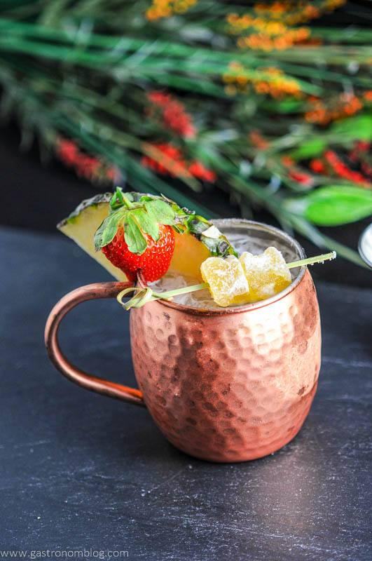Spicy Pineapple Strawberry Moscow Mule in copper mug with pineapple wedge, strawberry and ginger. Flowers in background