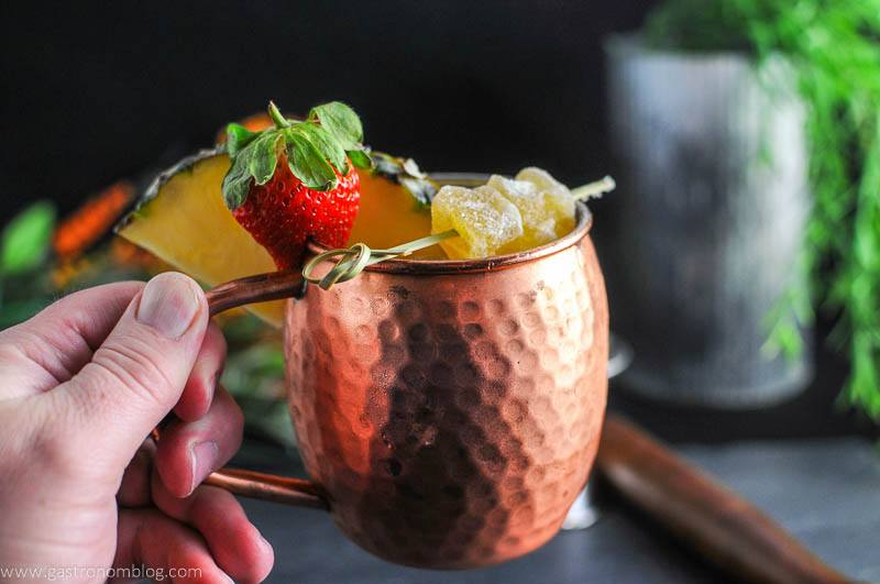 Spicy Pineapple Strawberry Moscow Mule in copper mug, strawberry and pineapple wedge. Crystalized ginger on pick. Held by a hand